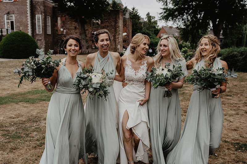 Braut mit Freundinnen auf dem Weg zur modernen Traumhochzeit.